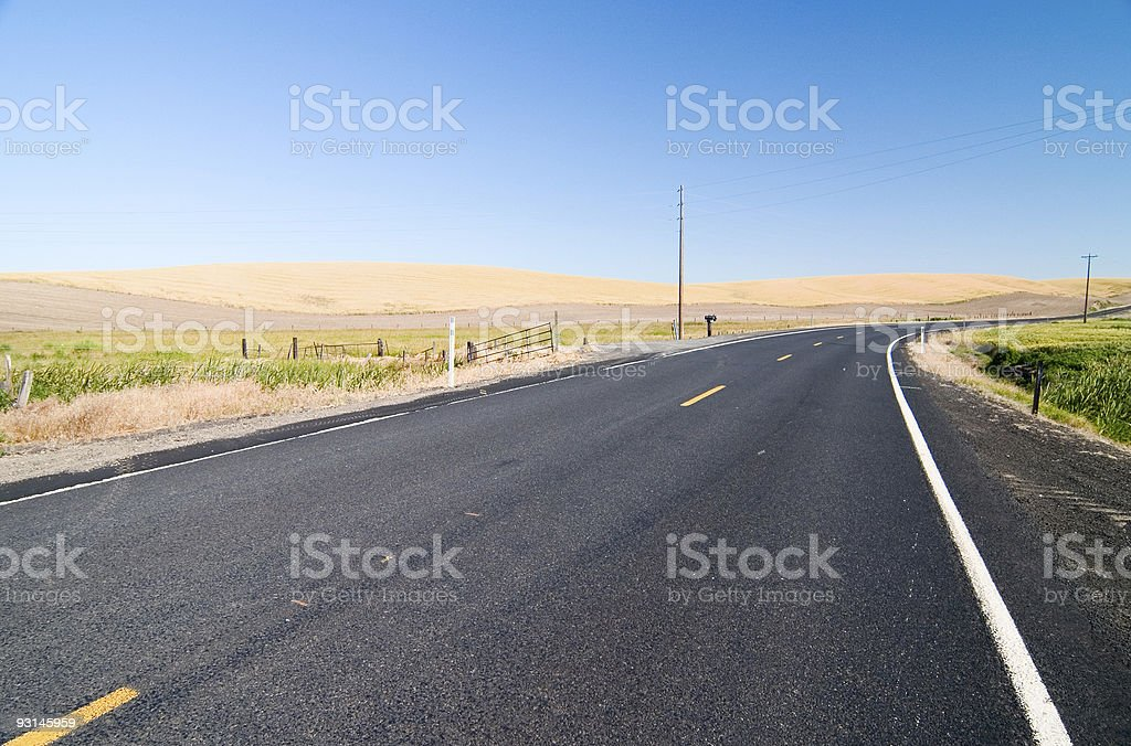 Rural road turning into the distance stock photo