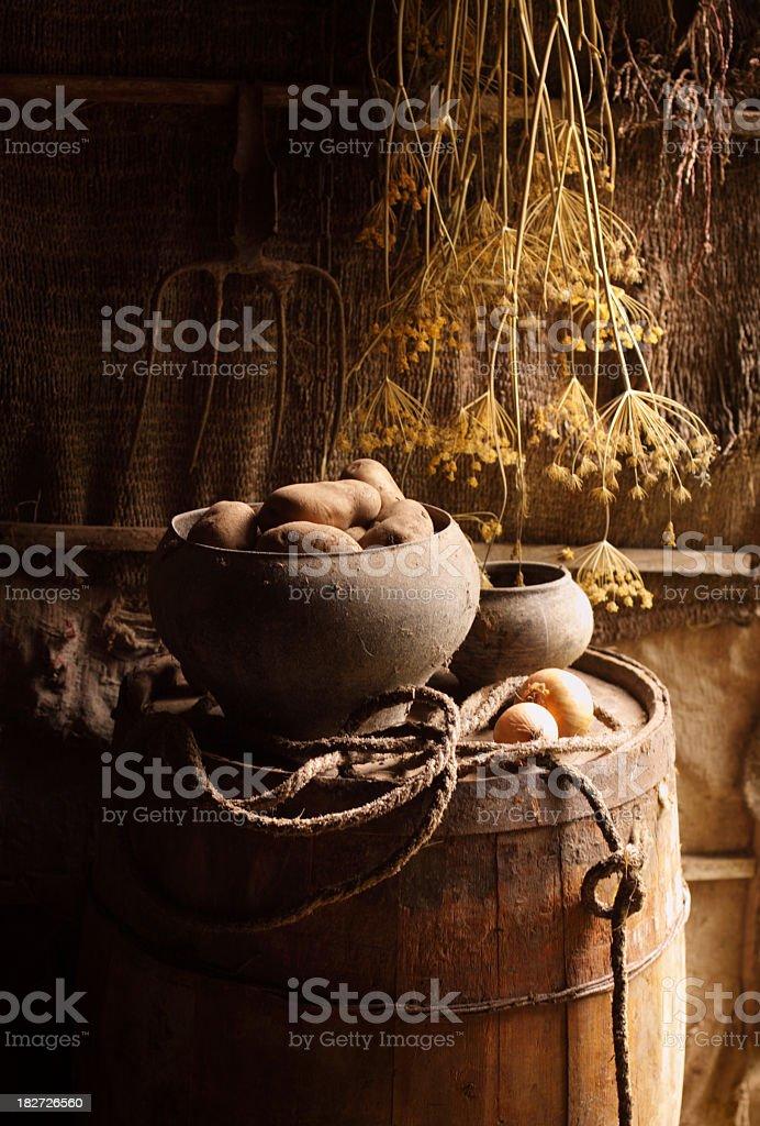 Rural still life with vintage pot, potato, onion,  old barrel royalty-free stock photo