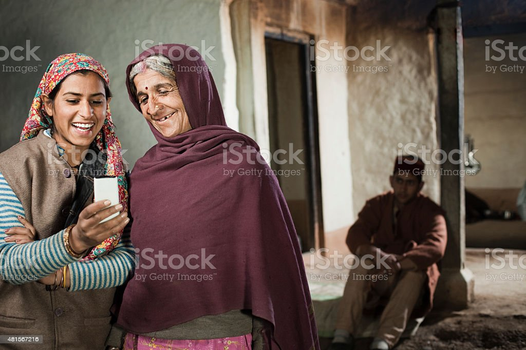 Rural teenage happy girl showing mobile phone to her grandmother. stock photo