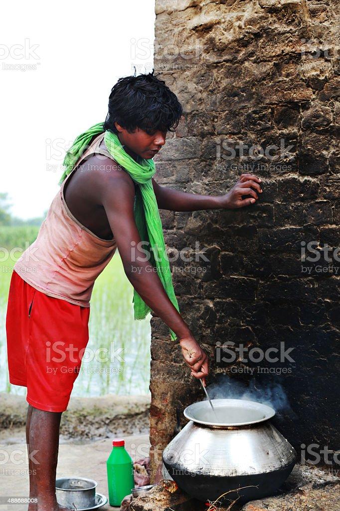 Rural Teenager Boy Preparing Food in Open Kitchen stock photo