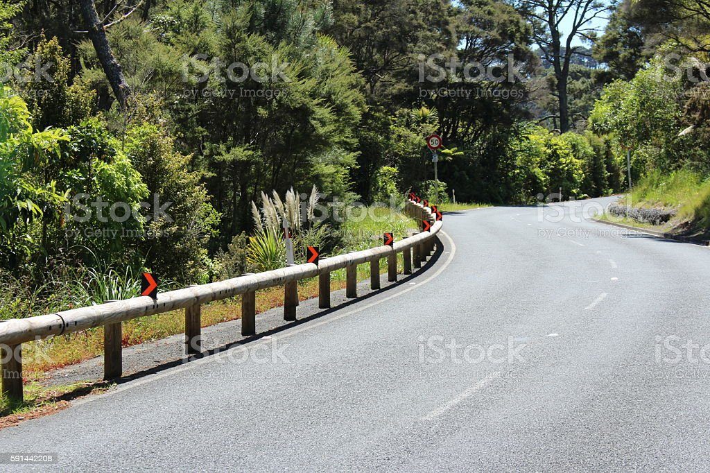 Rural windy road in New Zealand with road signs stock photo