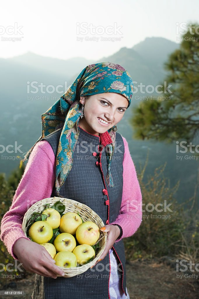 Rural woman holding apple basket looking at camera in mountains. stock photo