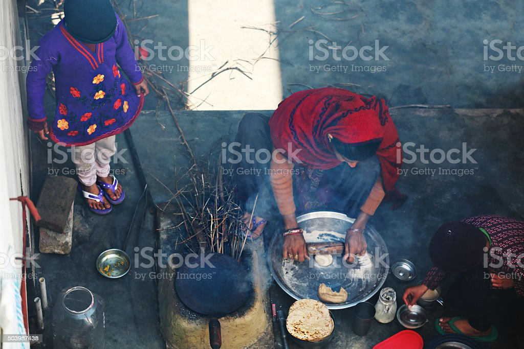 Rural women making chapatti on Wood burning stove (Chulha) stock photo