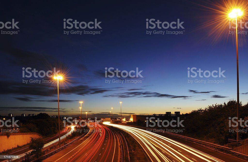 Rush hour on motorway with blurred headlights at dusk stock photo
