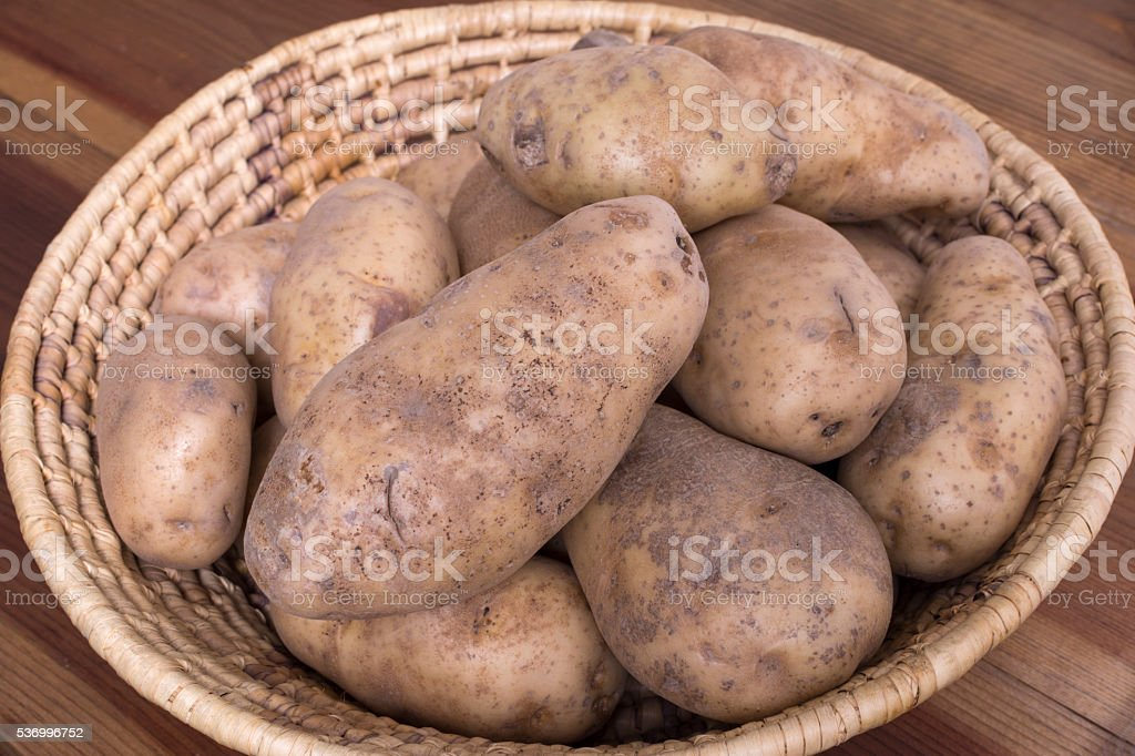 Russet potatoes in woven basket stock photo