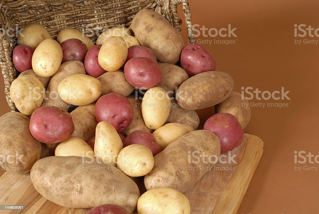 Russet, red and white potatoes spilling out of a basket stock photo