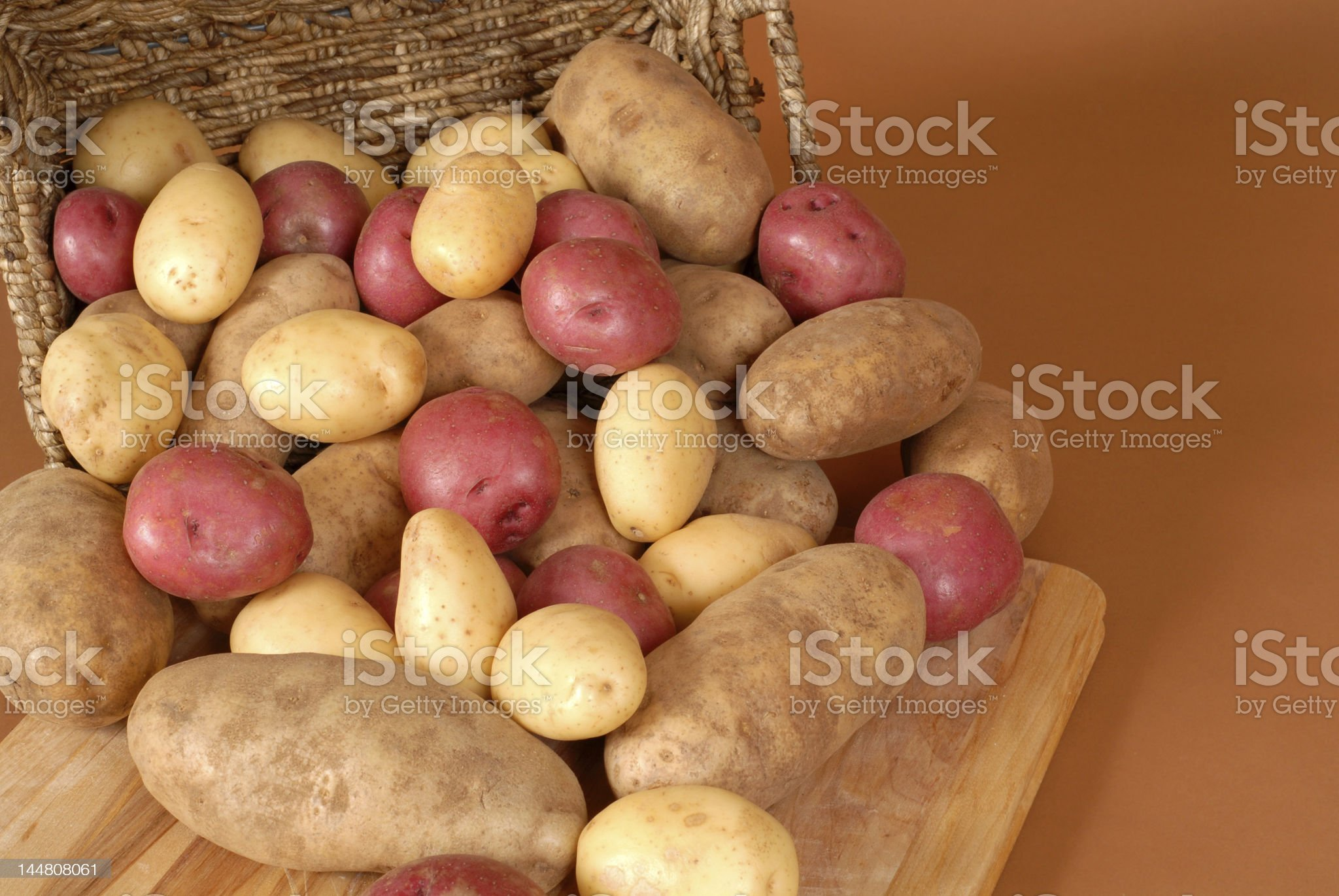 Russet, red and white potatoes spilling out of a basket royalty-free stock photo