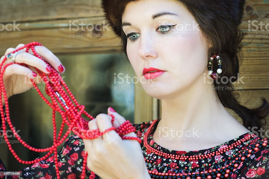 Russian beauty looking on red coral beads in raised arms stock photo