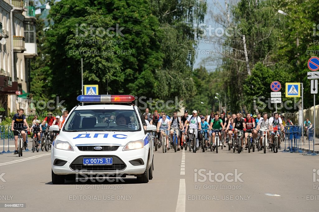 Russian Bikeday in Orel. Police car and bicyclists stock photo