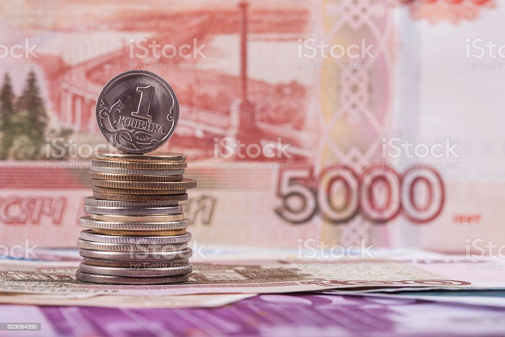 Russian coin kopeck on the background of ruble banknote stock photo