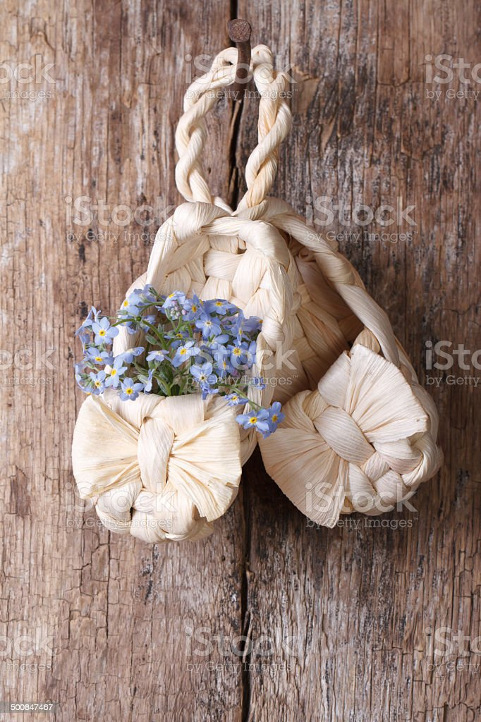 Russian decor: baby bast shoes with flowers forget-me-not. stock photo