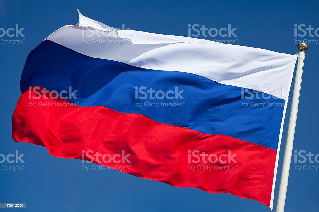 Russian flag flying against clear blue sky stock photo