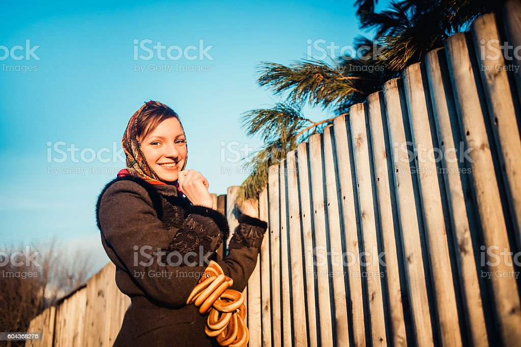Russian girl in national headscarves near wooden fence stock photo