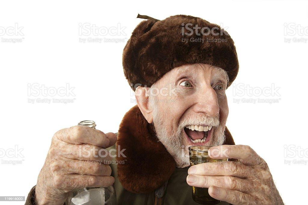 A Russian man in a fur cap drinking vodka stock photo