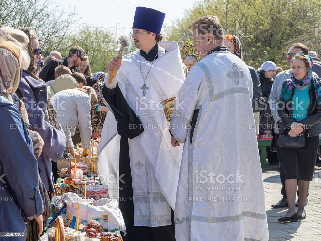 Russian Orthodox Church priest sprinkles Easter cakes and eggs stock photo