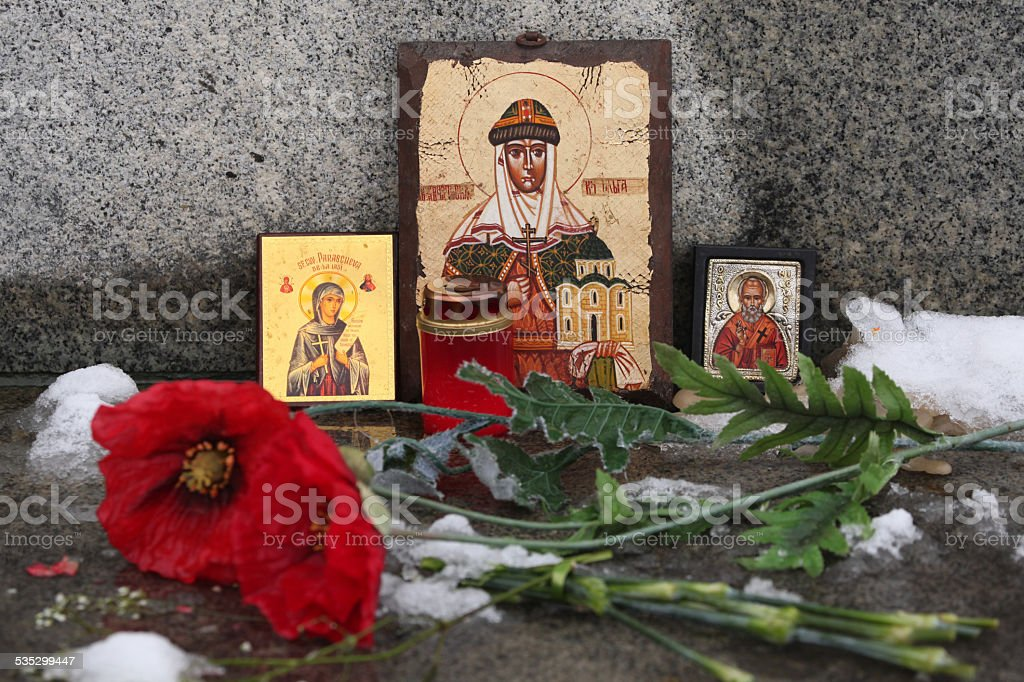 Russian orthodox icons and poppy flowers at a cemetery. stock photo
