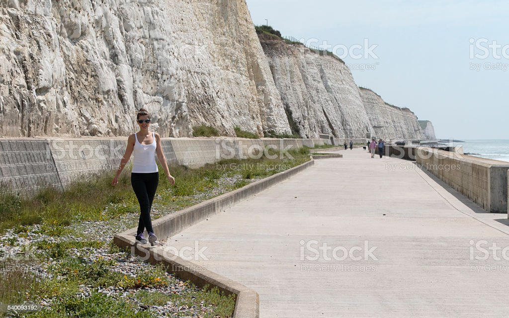 White cliffs Russian outdoor girl balancing on kerb stone stock photo