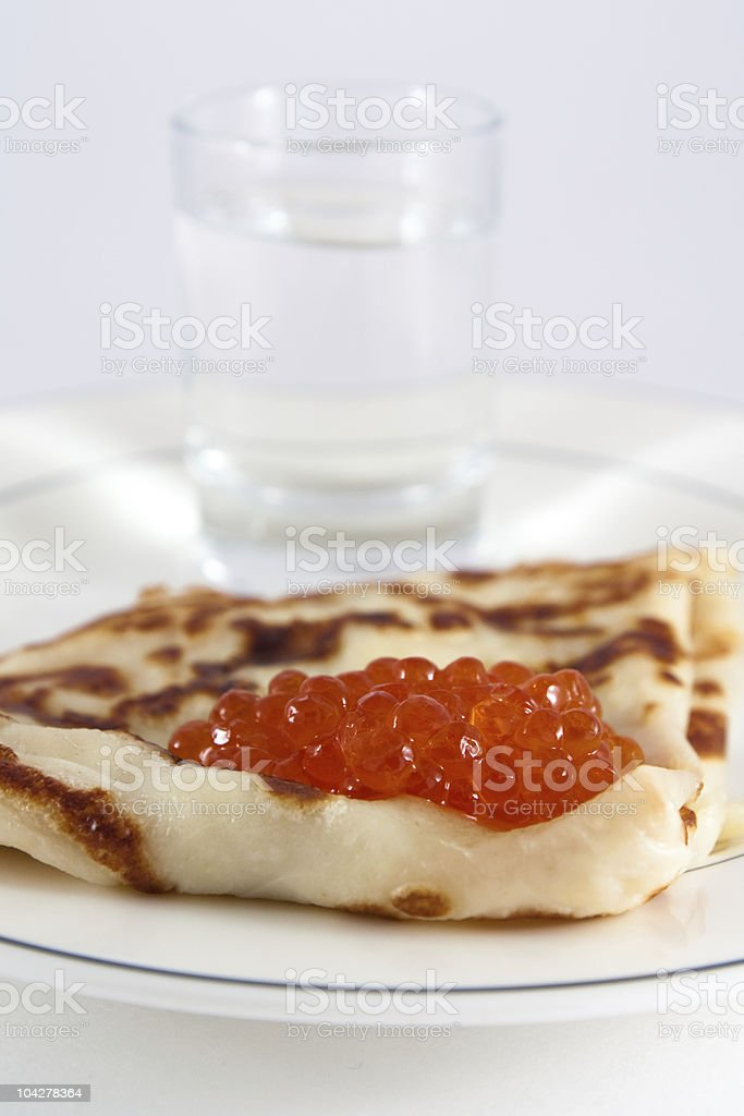 Russian pancake with red caviar and vodka stock photo