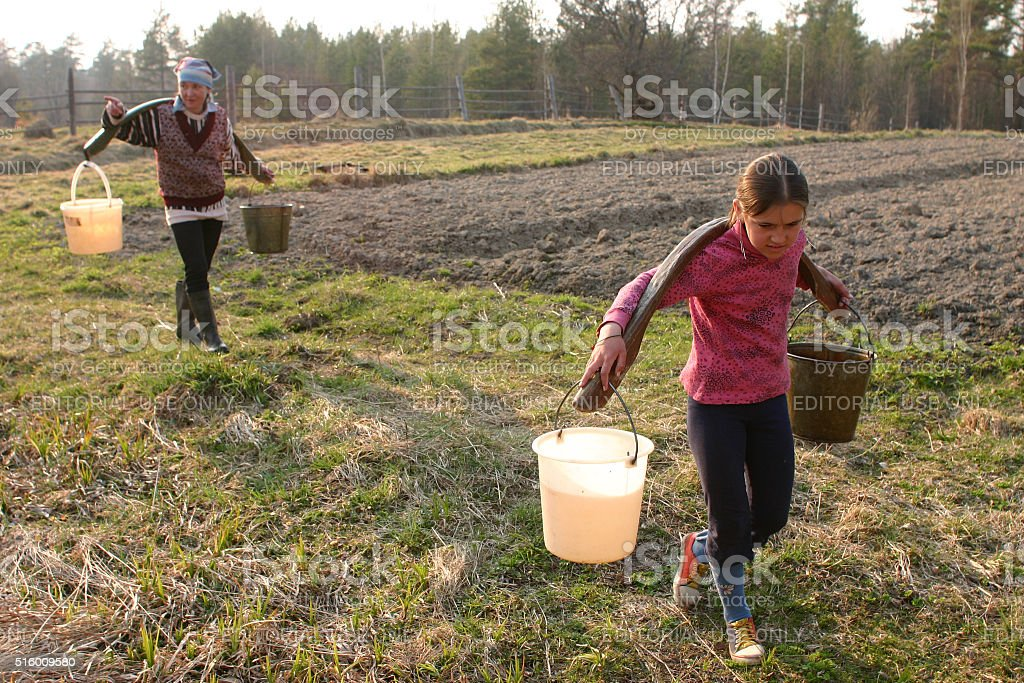 Russian peasant girl Carrying Water Buckets stock photo