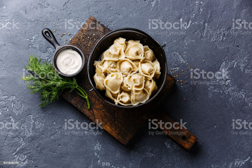 Russian pelmeni meat Dumplings with sauce sour cream stock photo