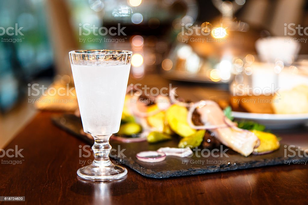 Russian vodka is poured into a frozen glass. stock photo