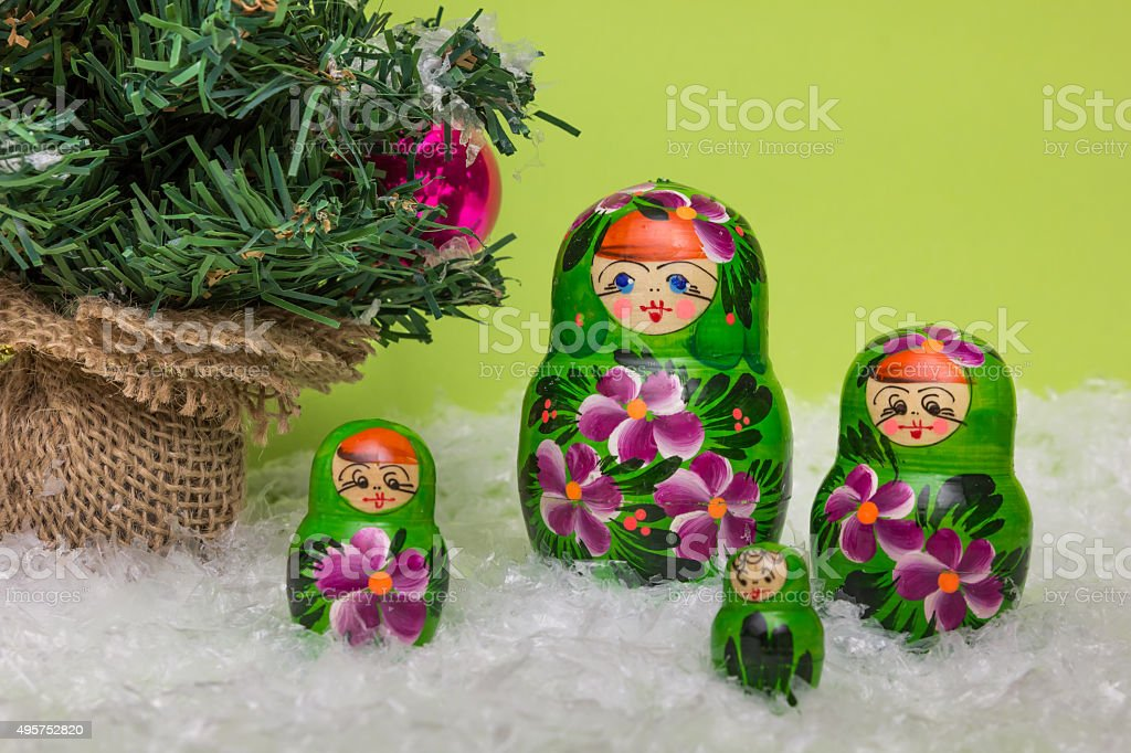 Russian wooden dolls with snow and Christmas tree stock photo