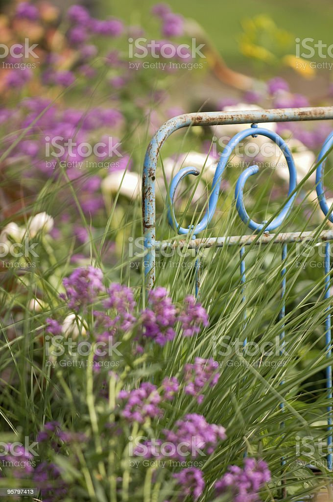 Rusted Bed Frame in Flower Garden royalty-free stock photo