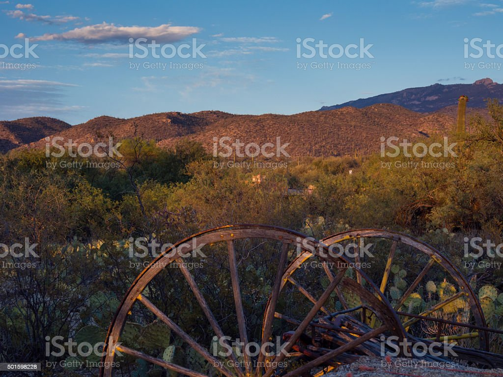 Rusted carriage weels in Arizona desert at sunset stock photo