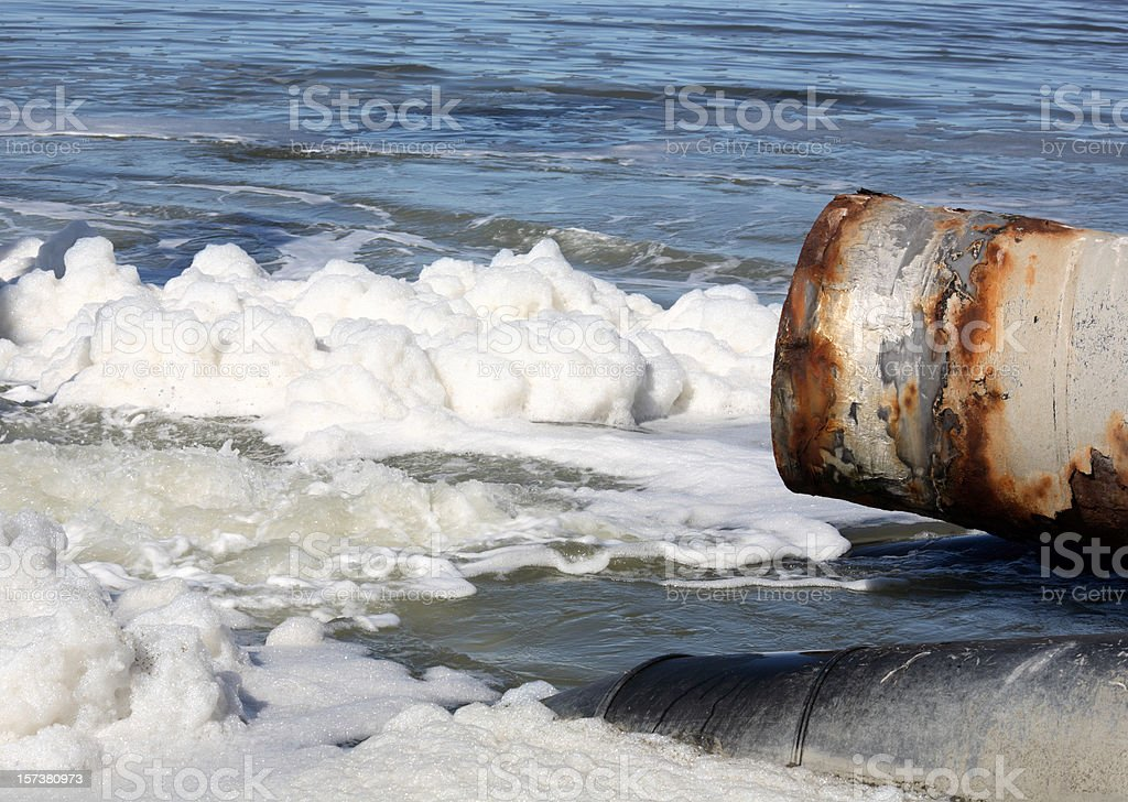 Rusted corroded old pipe spewing pollution out onto bay stock photo
