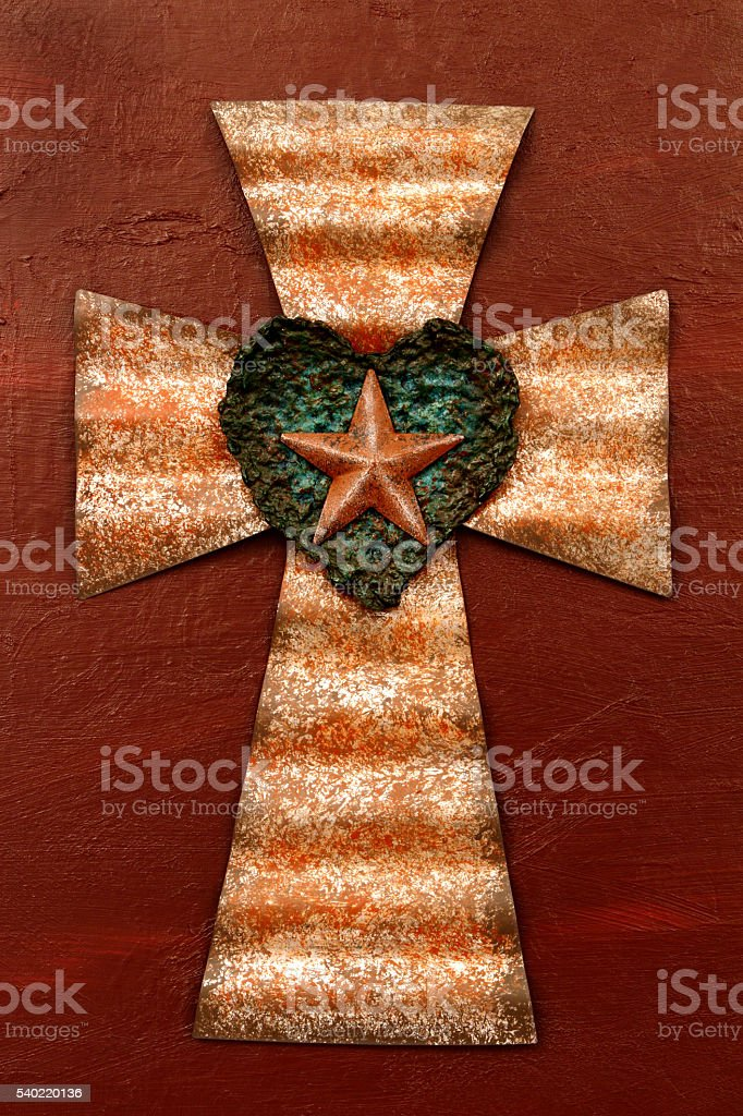 Rusted corrugated metal Cross on a painted dark red background stock photo