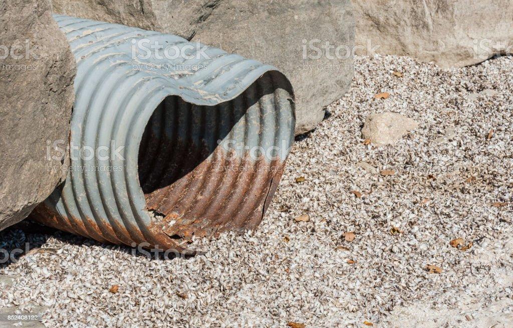 Rusted corrugated metal drain pipe betwen rocks. stock photo
