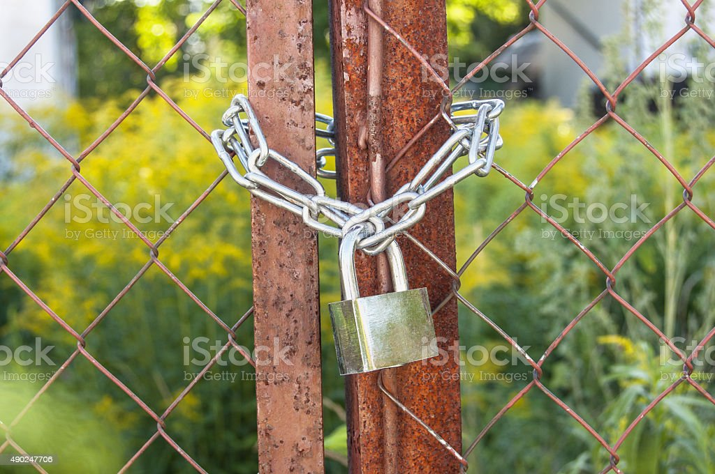 Rusted gate is lock with a chain and padlock stock photo