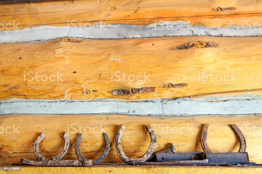 Rusted horseshoes placed on a shelf with a wooden wall background stock photo