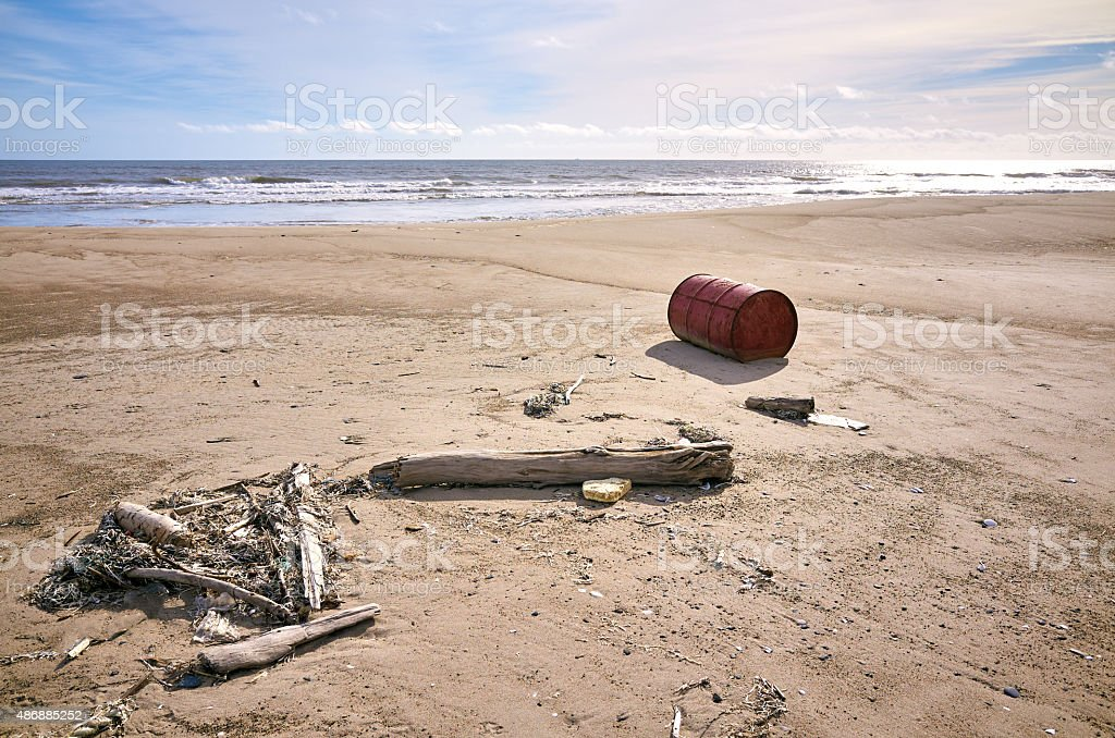 Rusted old barrel on sand beach and logs stock photo