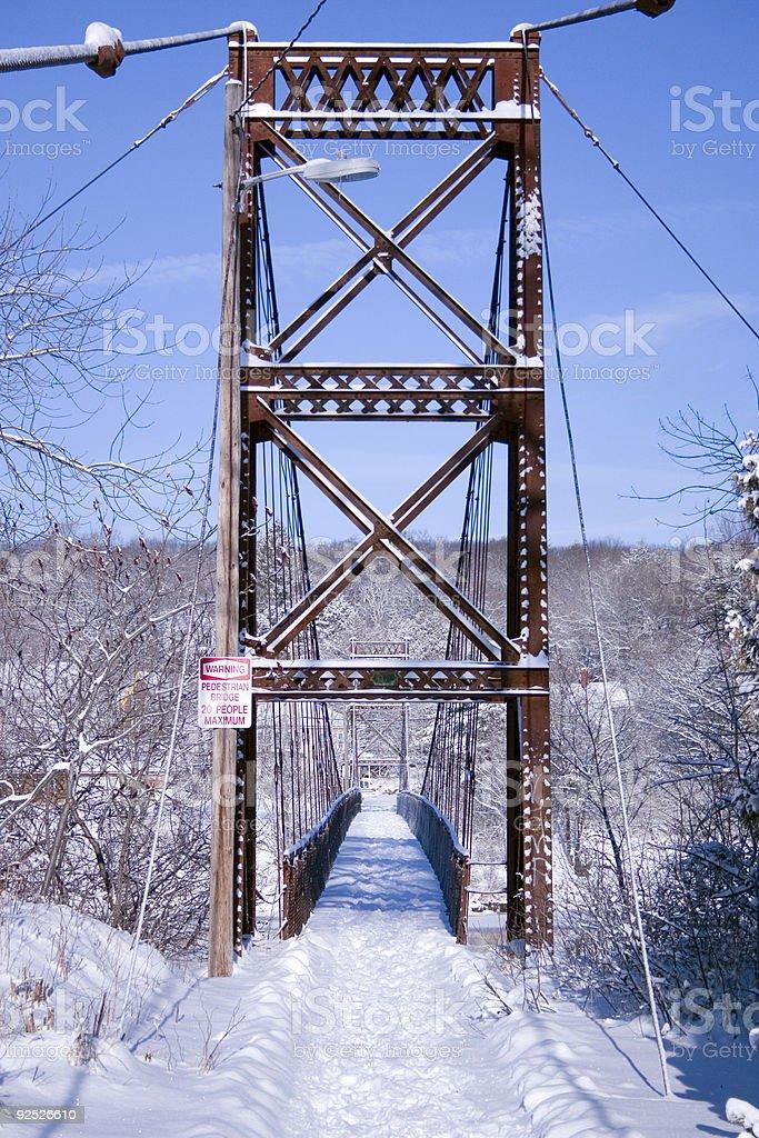 Rusted Pedestrian Suspension Bridge in Winter stock photo