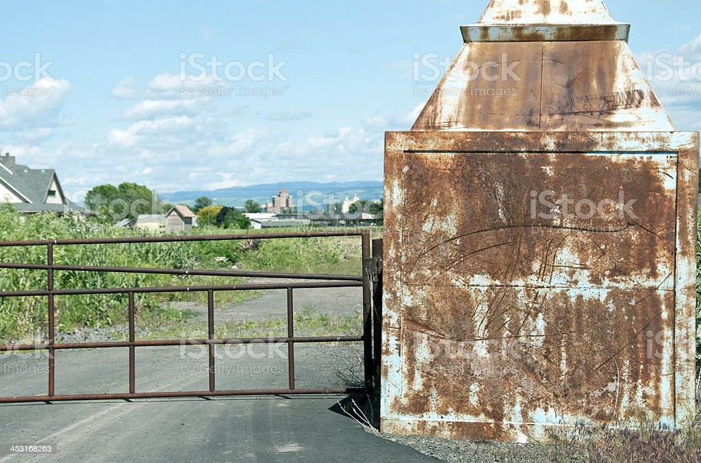 Rusted pillar and closed gate to empty land in Washington stock photo