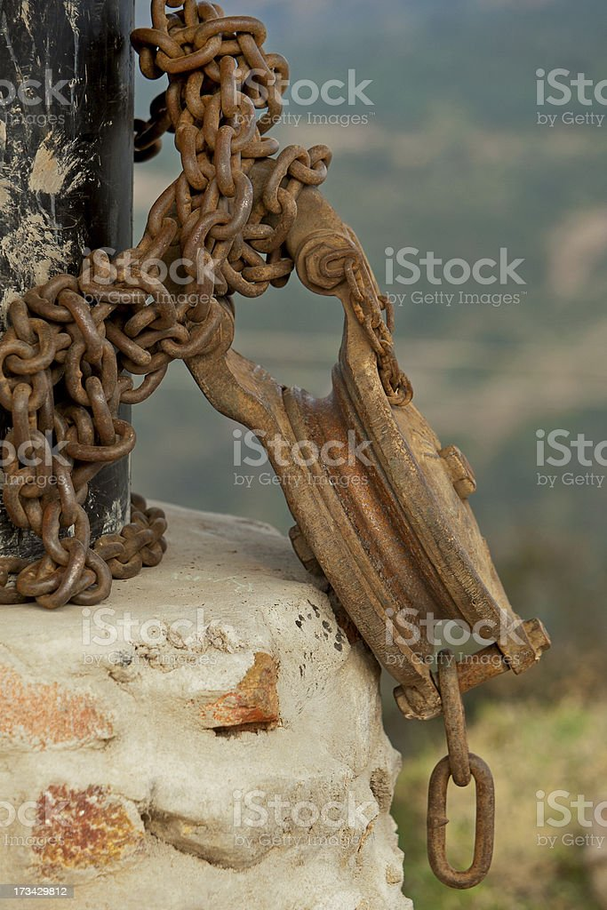 Rusted pulley chained to a pole royalty-free stock photo