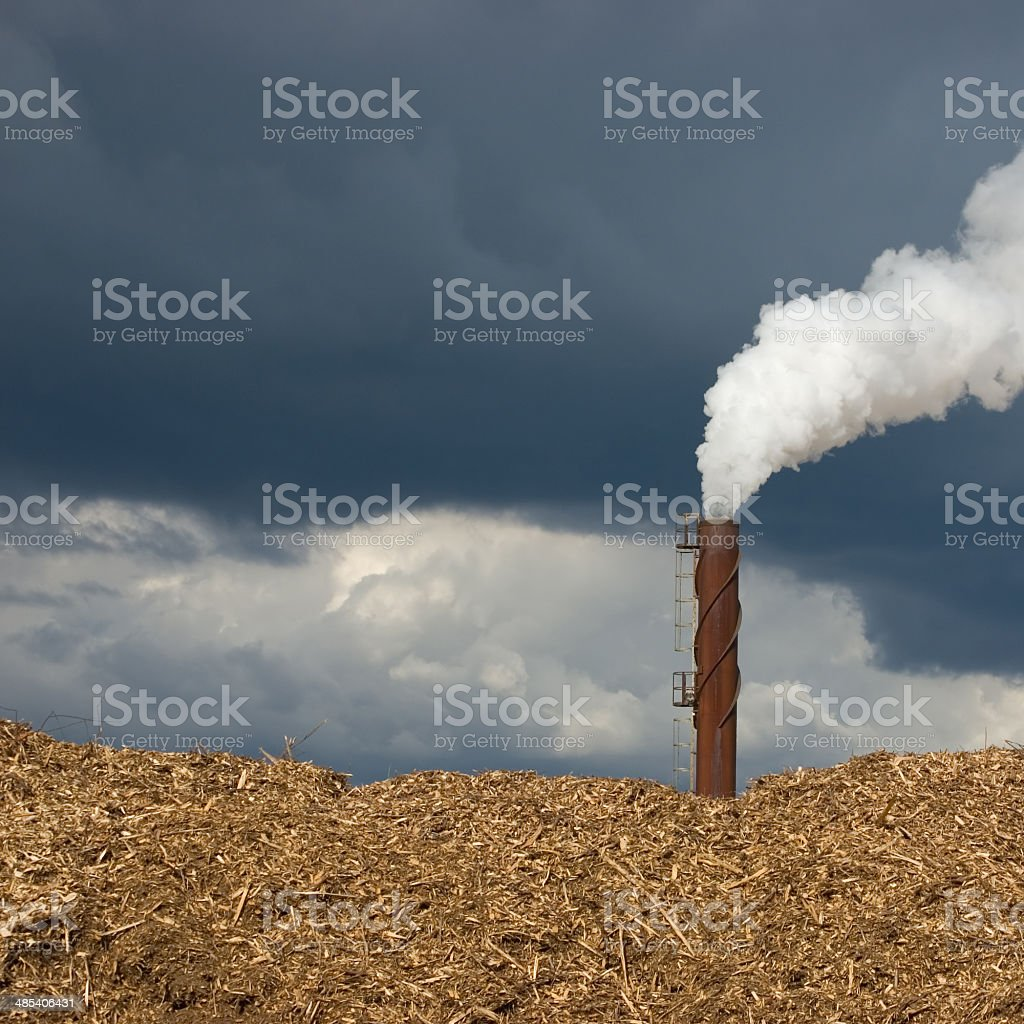 Rusted smokestack chimney, smoke steam, polluting closeup, beige woodchips stack stock photo