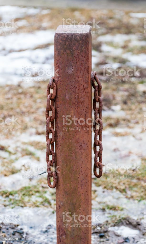Rusted square metal post with two hanging chains. stock photo