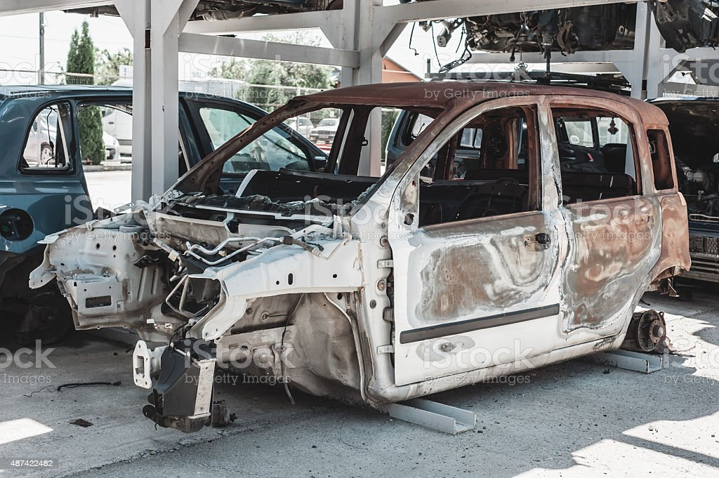 Rusted torched car in a dismantling yard. stock photo