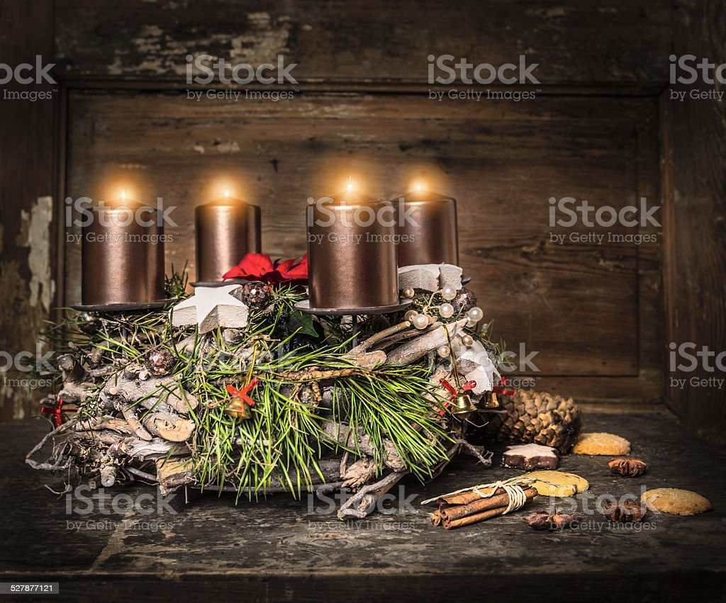 Rustic Advent wreath with four burning candles and traditional cookie stock photo