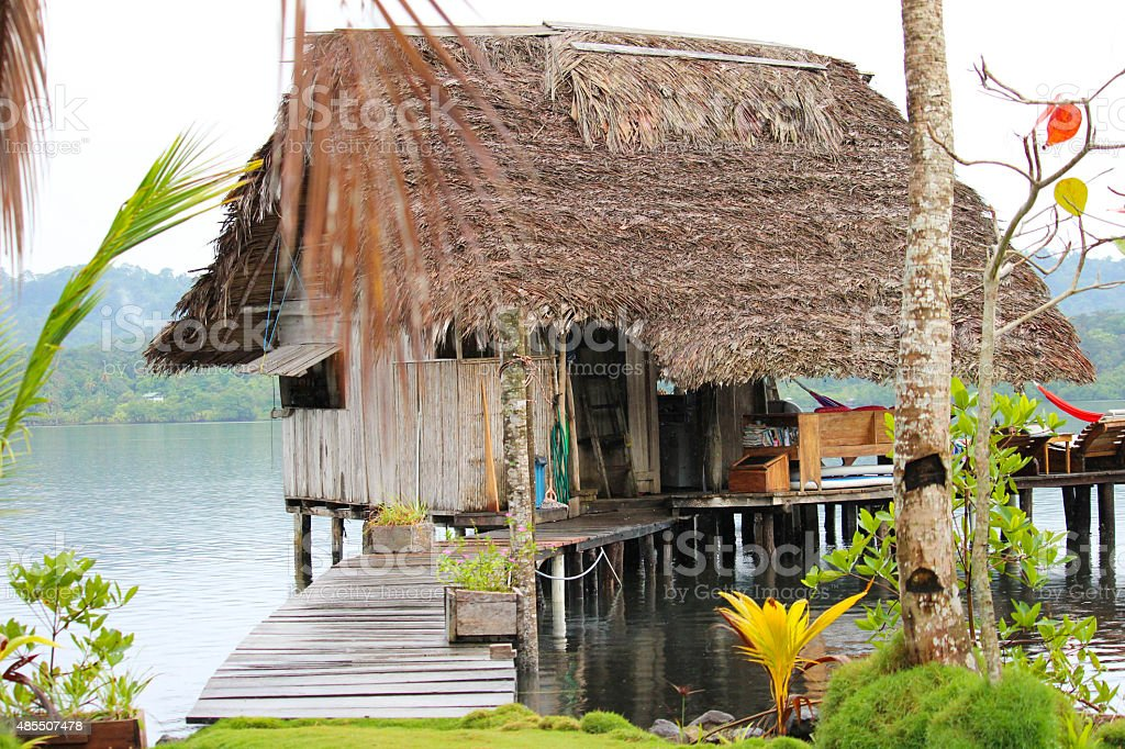 Rustic beach cabin on stilts over water on the beach stock photo