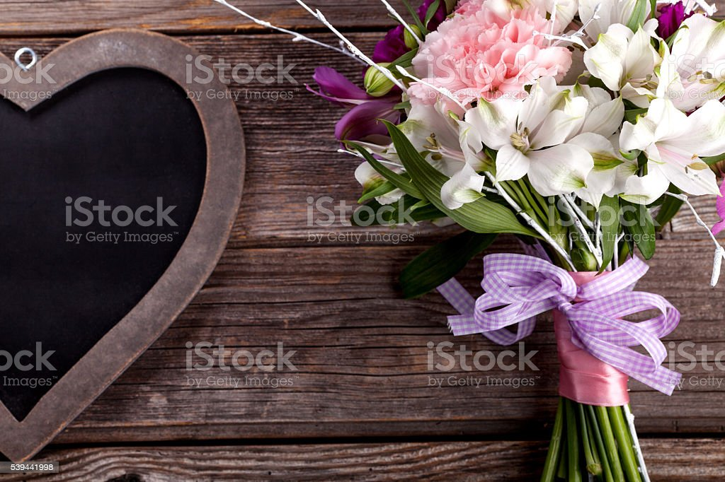 Rustic bouquet from gillyflowers and alstroemeria on old wooden stock photo