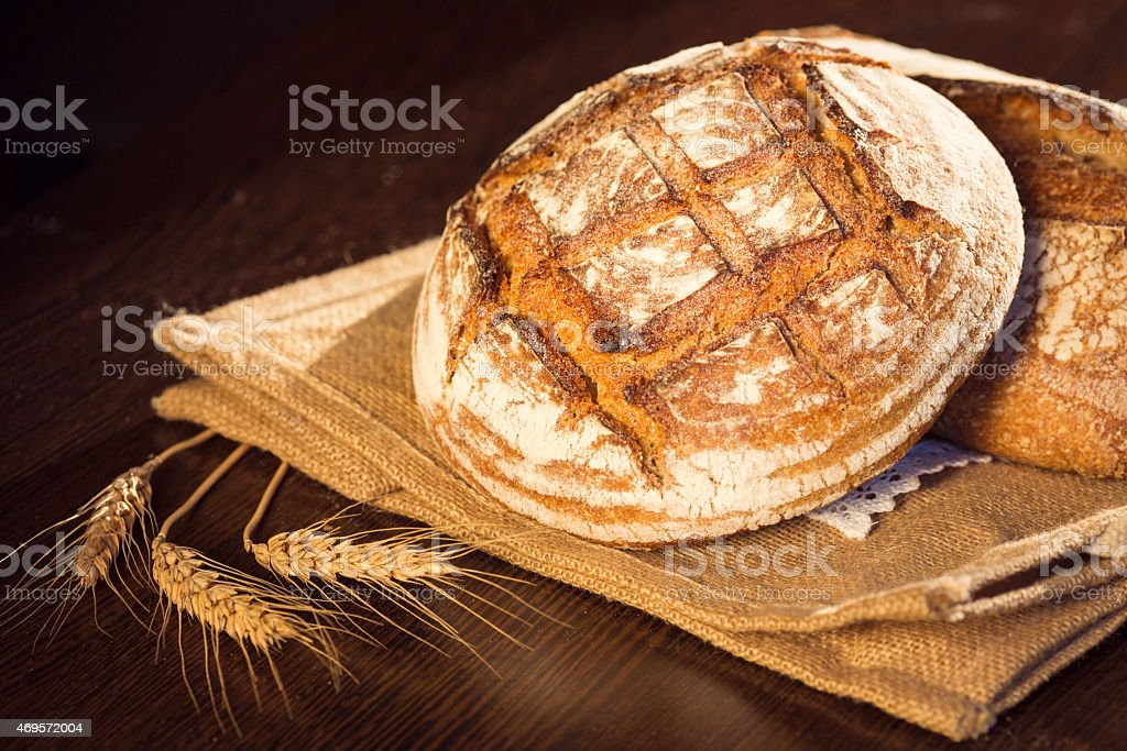Rustic bread and wheat on a traditional cloth bag stock photo