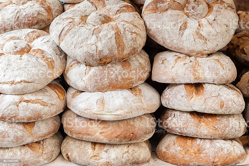 rustic bread in the foreground baked and placed in piles stock photo