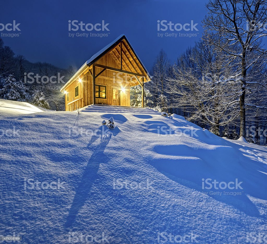 Rustic cabin in winter blizzard snowstorm at night royalty-free stock photo