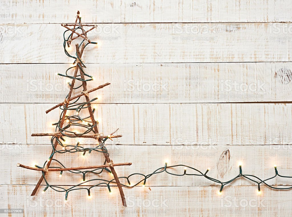 Rustic christmas tree lighted on textured wood background. stock photo