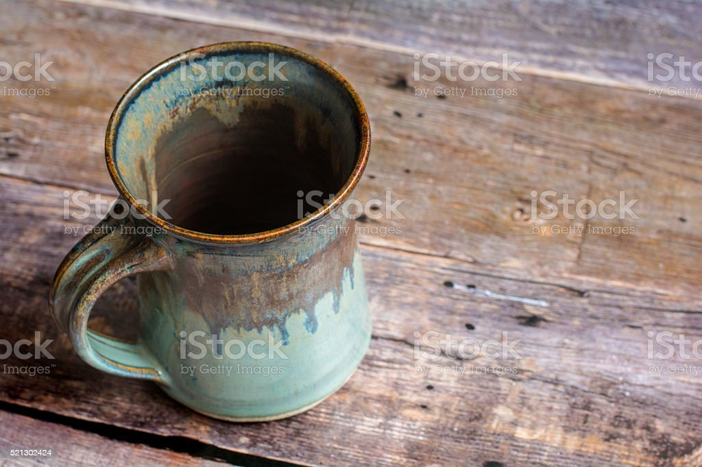 Rustic Clay Mug on a Old Barn Board Floor stock photo