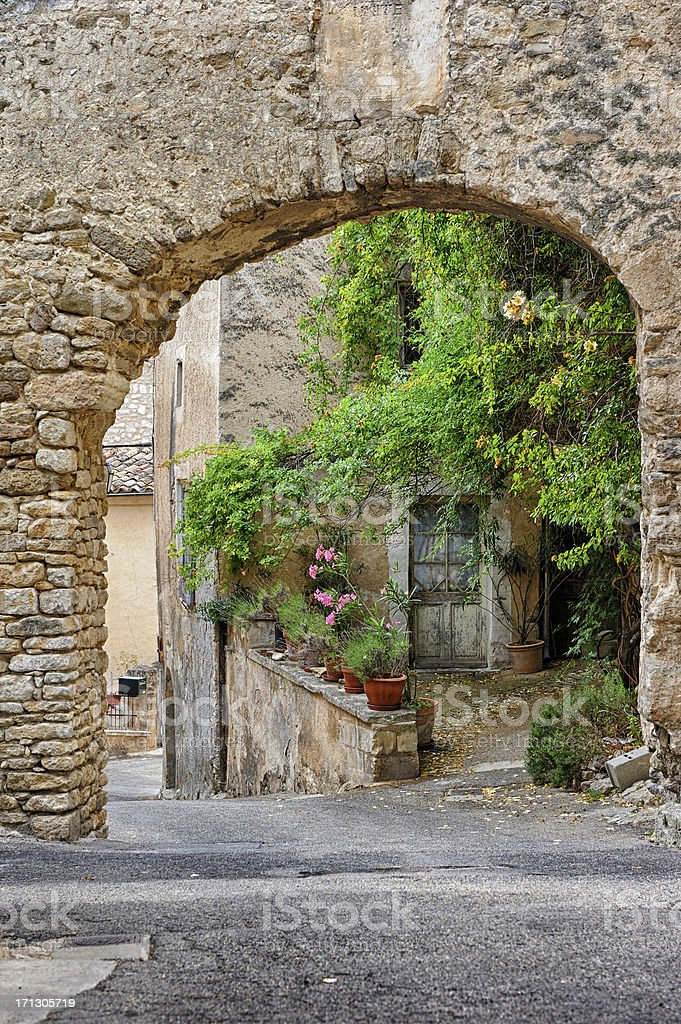 Rustic courtyard viewed through stone arch in Lacoste, France stock photo