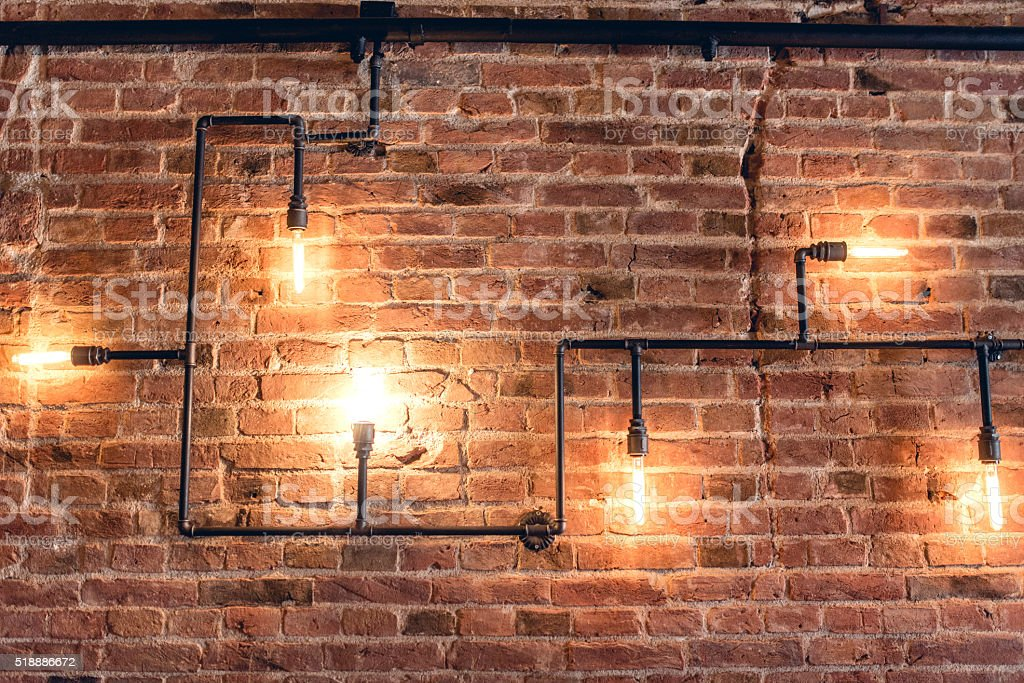 Rustic design, brick wall with light bulbs and pipes stock photo